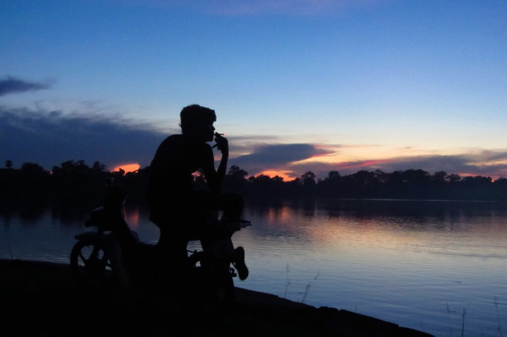 Using the back light to silhouette this motorbike driver at sunset. Sras Srong Lake, Siem Reap, Cambodia.
