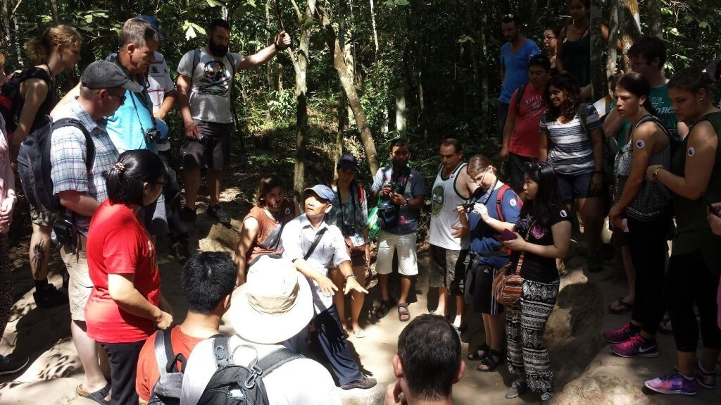 Letting the local guide take over and explain the Cu Chi Tunnels in Vietnam.